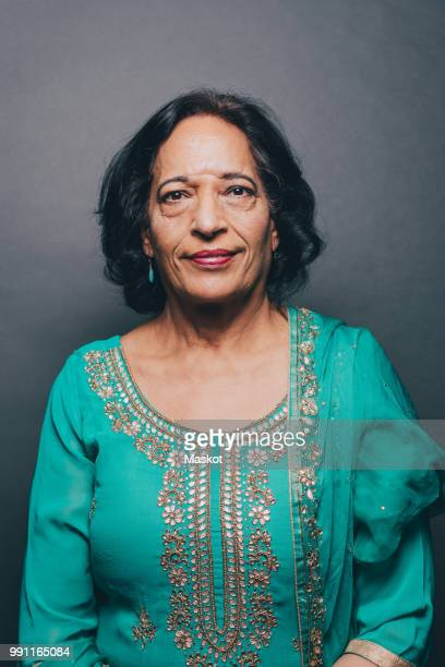 Portrait of confident senior woman wearing salwar kameez on gray background