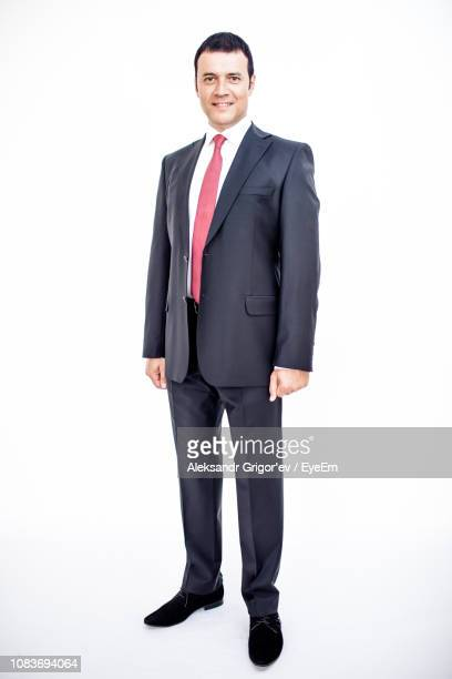 portrait of confident smiling businessman wearing suit standing against white background - full length stock pictures, royalty-free photos & images