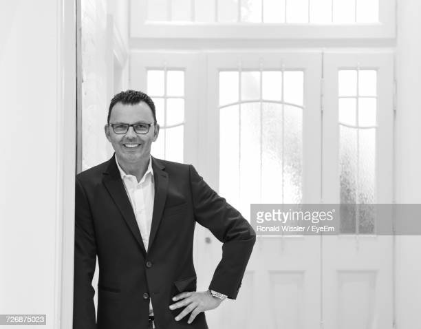 Portrait Of Confident Smiling Businessman With Hand On Hip Standing Against Door