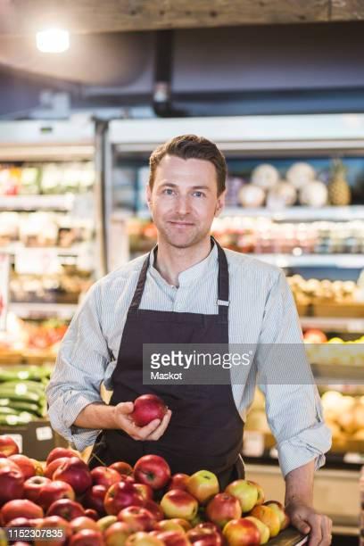 portrait of confident smiling entrepreneur holding apple while standing in supermarket - banca de mercado imagens e fotografias de stock