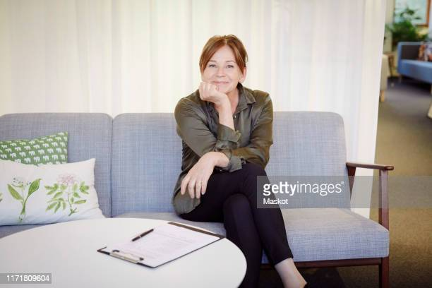 portrait of confident smiling female psychologist sitting on sofa at workshop - mental health professional stock pictures, royalty-free photos & images