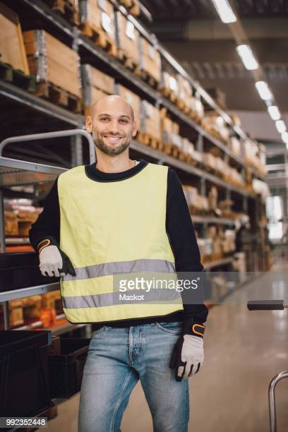 Portrait of confident smiling laborer standing by trolley at aisle in warehouse