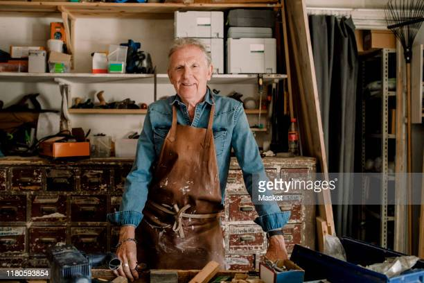 portrait of confident smiling senior male owner standing at workshop - craftsperson stock pictures, royalty-free photos & images