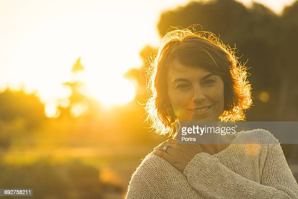 portrait of confident smiling woman during sunset - gegenlicht stock-fotos und bilder