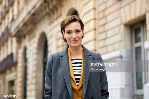 portrait of confident smiling woman in city - long coat stock pictures, royalty-free photos & images