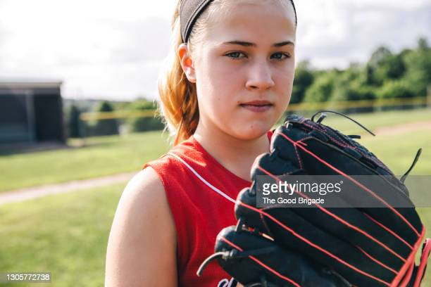 portrait of confident softball player holding glove on baseball field - baseball strip stock pictures, royalty-free photos & images