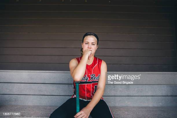 portrait of confident softball player leaning on bat in dugout - baseball strip stock pictures, royalty-free photos & images