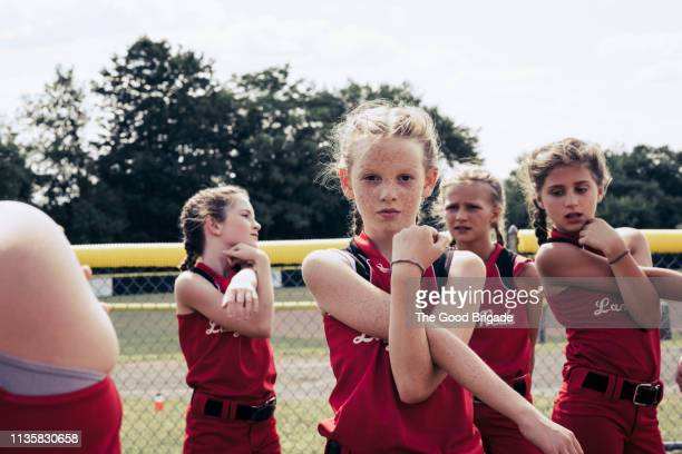 portrait of confident softball player stretching - softball sport stock pictures, royalty-free photos & images