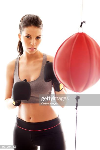 Portrait of confident sportswoman standing by punching bag against white background