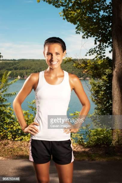 portrait of confident sportswoman standing on road - sportlerin stock-fotos und bilder