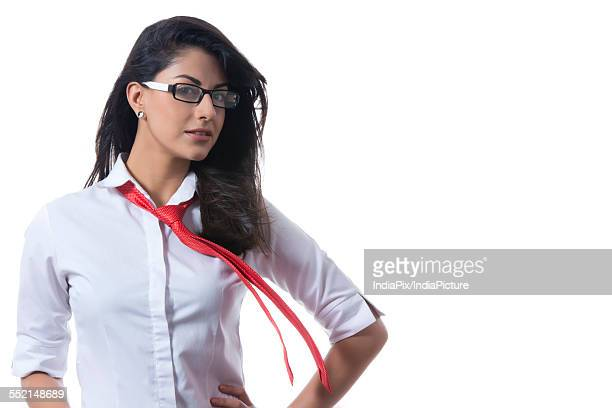 Portrait of confident stylish businesswoman with windswept tie against white background