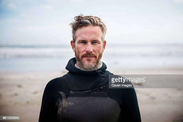 portrait of confident surfer standing at beach - wetsuit stock pictures, royalty-free photos & images