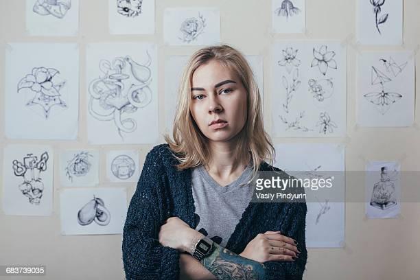 Portrait of confident tattoo artist standing against designs at art studio