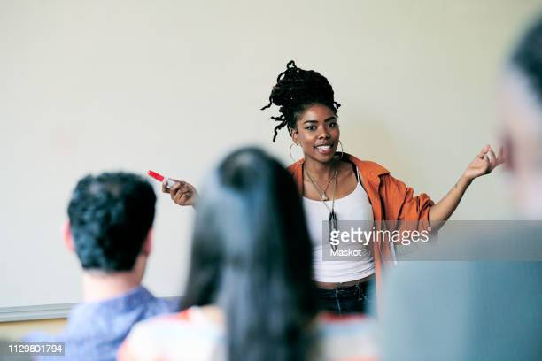portrait of confident teacher gesturing while teaching students in language class - teaching stock pictures, royalty-free photos & images