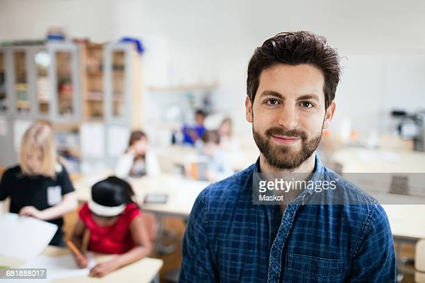 portrait of confident teacher with students studying in background - lehrkraft stock-fotos und bilder