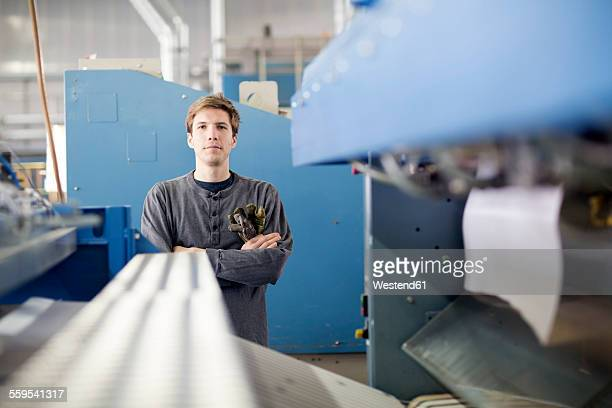 Portrait of confident technician between machines