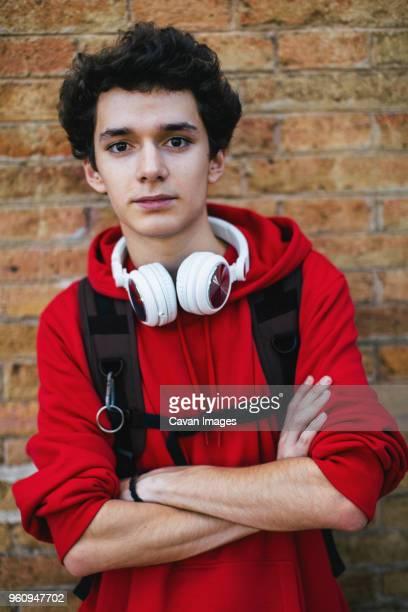portrait of confident teenage boy with backpack and arms crossed standing against brick wall - un seul jeune garçon photos et images de collection
