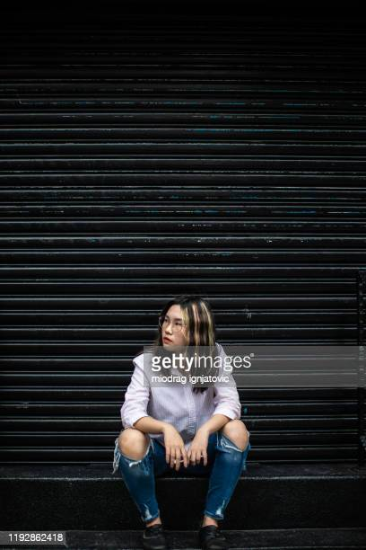 portrait of confident teenage girl sitting on steps - industrial door stock pictures, royalty-free photos & images