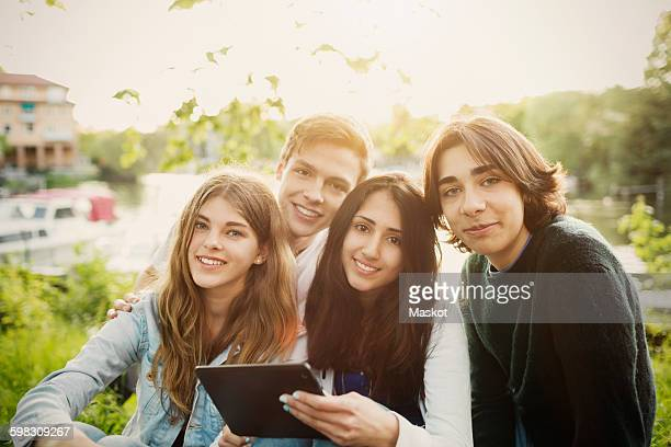 portrait of confident teenagers with digital tablet at park - quatro pessoas - fotografias e filmes do acervo