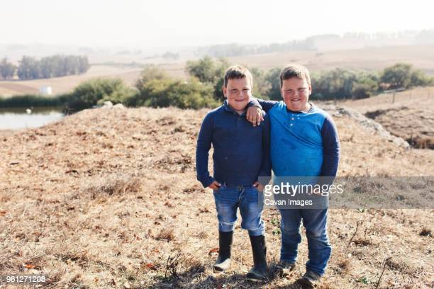 portrait of confident twin brothers standing on field against clear sky during sunny day - fat kid stock photos and pictures