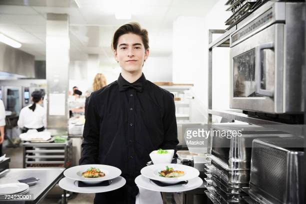 portrait of confident waiter holding dishes in commercial kitchen - waiter stock pictures, royalty-free photos & images