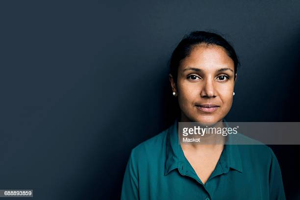 portrait of confident woman against gray background - femme indienne photos et images de collection