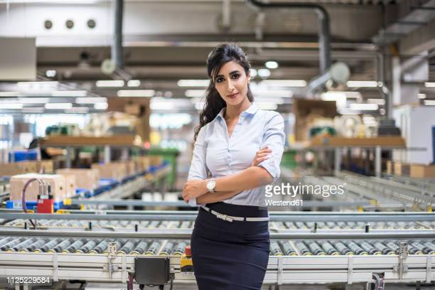 portrait of confident woman at conveyor belt in factory - three quarter length stock pictures, royalty-free photos & images