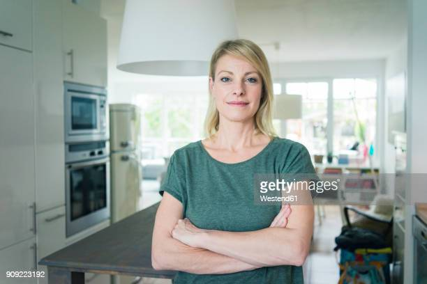 portrait of confident woman at home - arme verschränkt stock-fotos und bilder