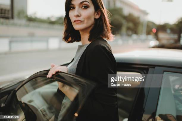 Portrait of confident woman boarding into car in city