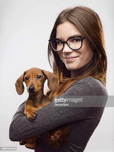 portrait of confident woman carrying dachshund - dachshund stock pictures, royalty-free photos & images