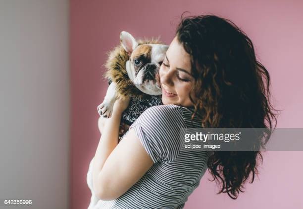 Portrait of confident woman carrying french bulldog
