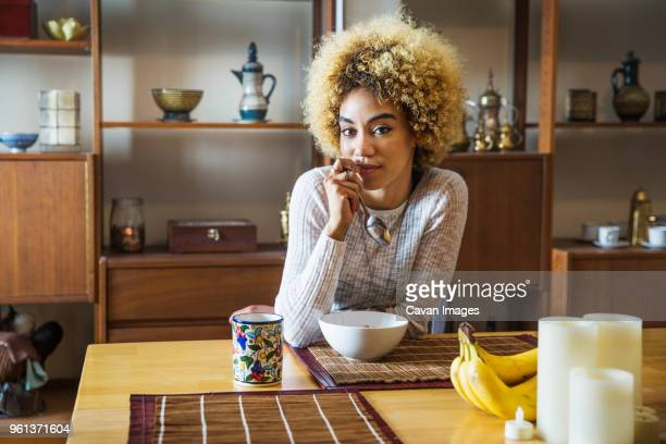 Portrait of confident woman holding spoon while sitting at table in house