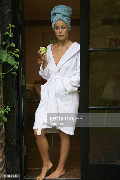Portrait of confident woman in bathrobe holding apple while standing at doorway