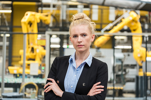 Portrait of confident woman in factory shop floor with industrial robot - gettyimageskorea