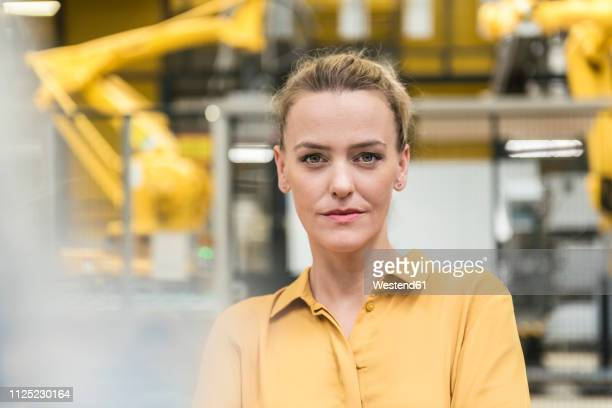 portrait of confident woman in factory shop floor with industrial robot - metallic look stock-fotos und bilder