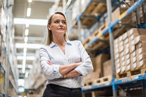 Portrait of confident woman in factory storehouse - gettyimageskorea