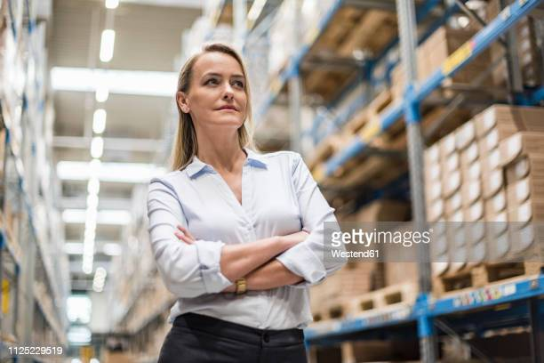 portrait of confident woman in factory storehouse - metallic look stock-fotos und bilder