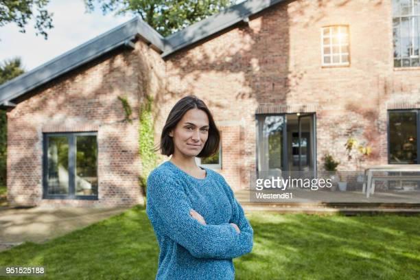 portrait of confident woman in garden of her home - arme verschränkt stock-fotos und bilder