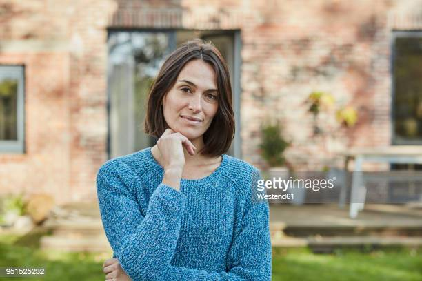 portrait of confident woman in garden of her home - in den dreißigern stock-fotos und bilder