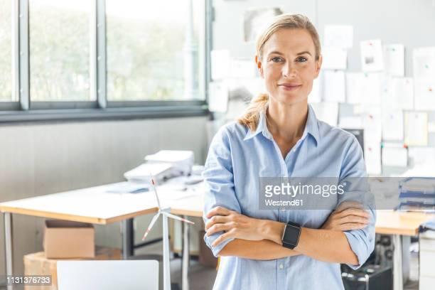 portrait of confident woman in office - tenue d'affaires photos et images de collection
