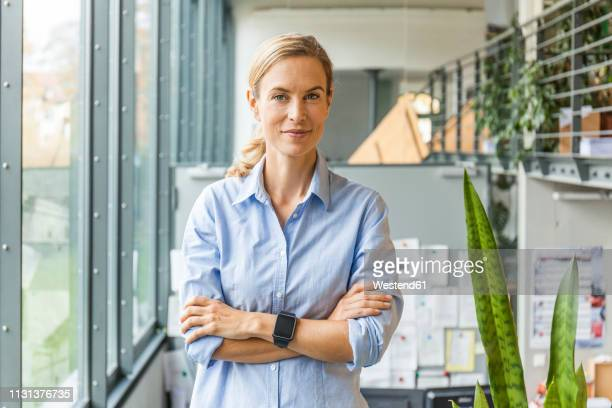portrait of confident woman in office - trabalhadora de colarinho branco - fotografias e filmes do acervo