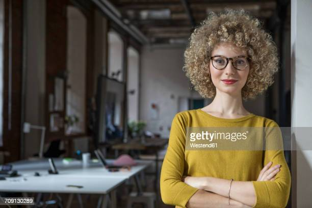 portrait of confident woman in office - blonde glasses stock-fotos und bilder