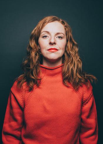 Portrait of confident woman in orange top over gray background - gettyimageskorea