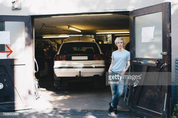 portrait of confident woman leaning on door at entrance of auto repair shop - auto repair shop exterior stock pictures, royalty-free photos & images