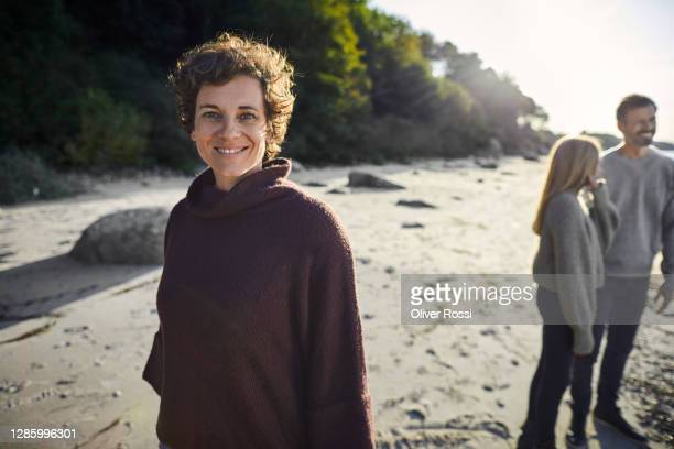 portrait of confident woman on the beach with family in background - 40 49 years stock pictures, royalty-free photos & images