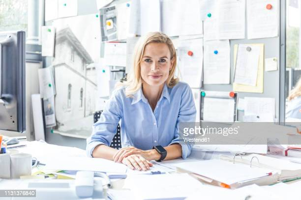 portrait of confident woman sitting at desk in office surrounded by paperwork - blonde hair stock pictures, royalty-free photos & images