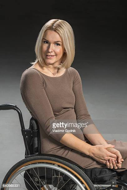 portrait of confident woman sitting in wheelchair - paraplegic woman stock photos and pictures