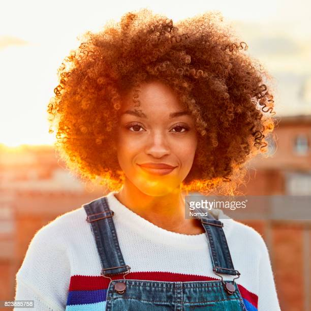Portrait of confident woman smiling at rooftop