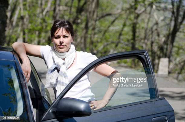 Portrait Of Confident Woman Standing By Car Against Trees