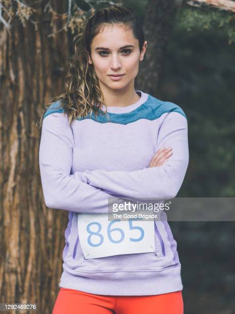 portrait of confident woman standing with arms crossed in forest - marathon stock pictures, royalty-free photos & images